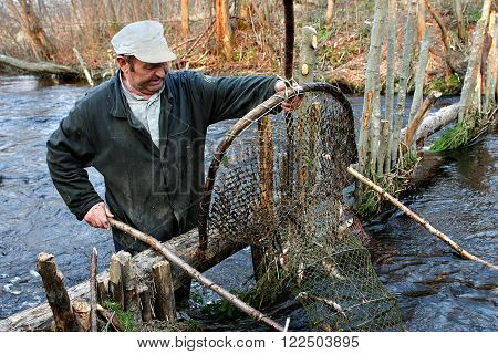 Tver, Russia - May 3 2006: Elderly peasant fishermen catch fish in a small river using hoop nets fish trap.