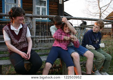 Tver, Russia - May 5 2006: Rural sittings near the wooden house an adult woman and three children having fun relaxing on a bench.