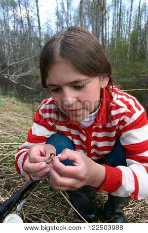 Tver,  Russia - May 6 2006: Rural teenager girl Tanya Shchegolev 11 years old the spring fishing skewer a worm on a hook.