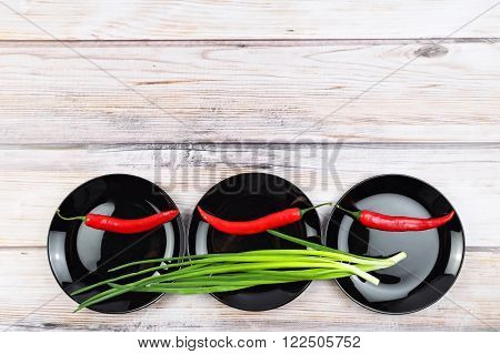 Red hot chilli pepper and scallions on black plate