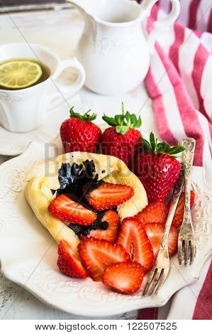 Fresh strawberry and crepes with cup of tea on vintage background