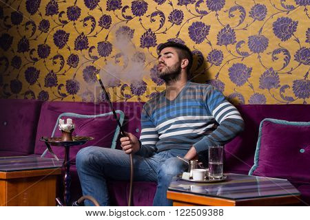 Man Smoking The Traditional Hookah