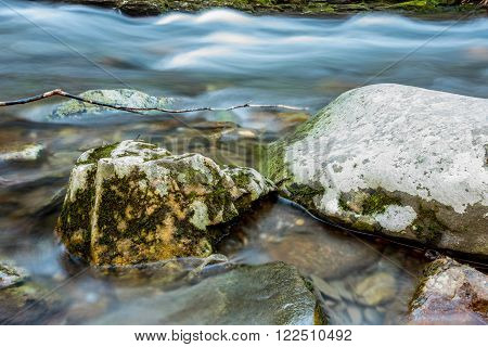 Snow melt rushing past mossy boulders in a creek in the Great Smoky Mountains National Park