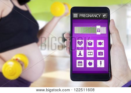 Image of pregnancy applications on the mobile phone screen and pregnant woman doing workout with dumbbells at gym