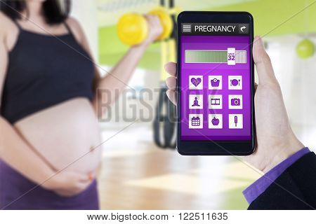 Close up of pregnant mother doing exercise with dumbbell at gym and pregnancy app on the mobile phone screen