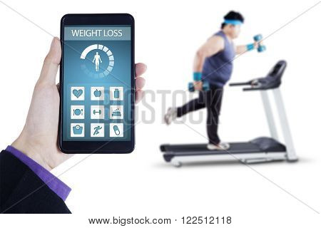 Picture of weight loss application on the mobile phone screen with overweight man exercising on treadmill