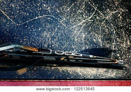 Old rusty rear-window screen wiper on dirty scratched window