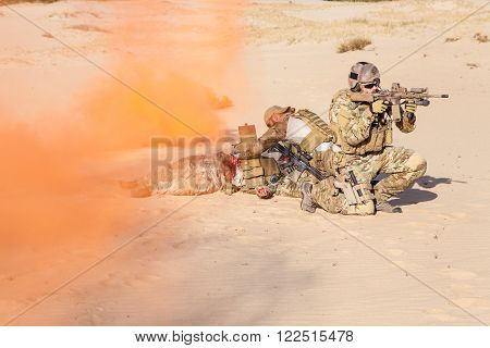 Squad of soldier evacuate the injured fellow in arms hiding in the smoke