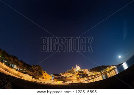 The starry sky captured on the coastline and historical town of Cervo, Ligurian Riviera, famous travel destination in Italy, glowing under moonlight. Scenic distortion by fisheye lens.
