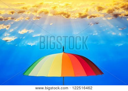 Rainbow umbrella against the sky and the sun shining.