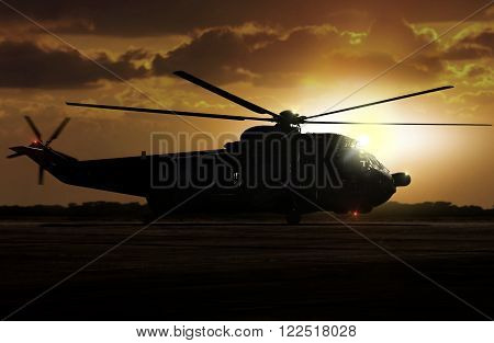 Military helicopter landed on airfield during sunset