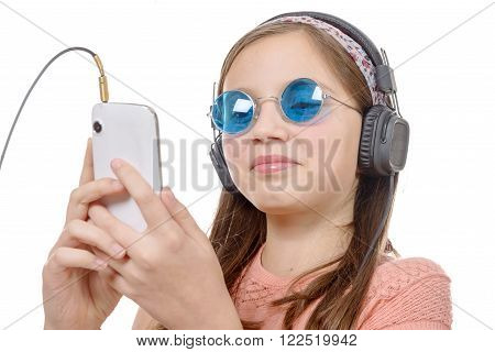 A preteen girl listening to music with his smartphone on white