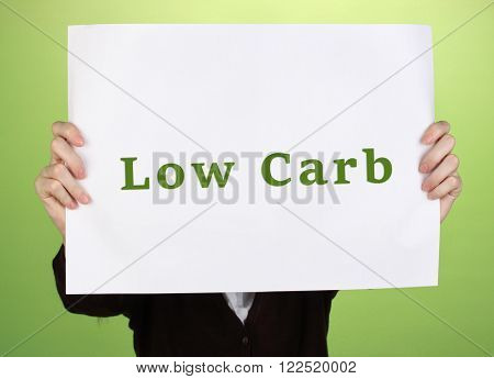 Woman holding paper with Low-Carb text on color background