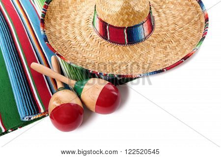 Traditional Mexican serape blanketor rug with sombrero and maracas isolated against a white background. Space for copy.