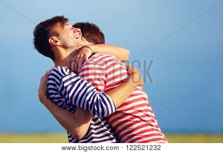 happy young male couple embracing outdoors, spring