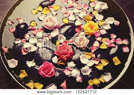 Pink, yellow rose petals and black stones in glass bowl with water, close up