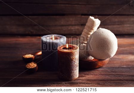Spa composition with alight candles and massage balls on wooden background