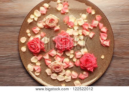 Pink rose petals in golden bowl with water on wooden background