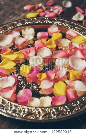 Pink and yellow rose petals in silver bowl on wooden background
