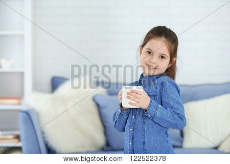 Little girl holding cup of water in living room