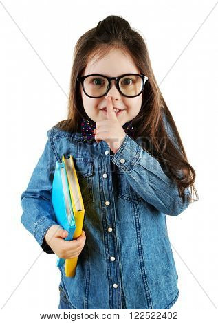 Cute little girl with notebooks holding finger on her moth isolated on white