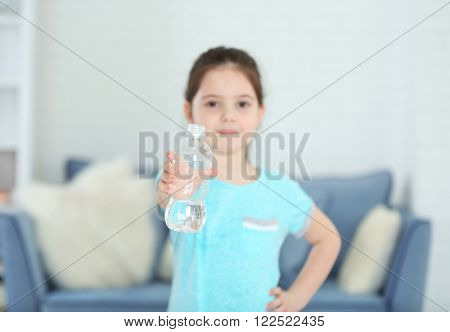 Little girl showing plastic bottle of water in living room