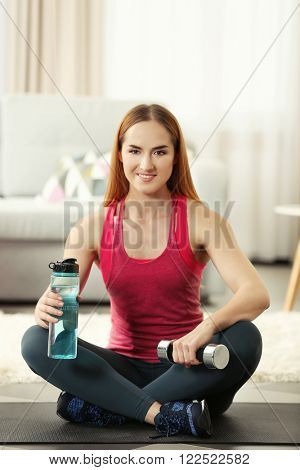 Young sportswoman sitting with bottle of water and dumbbells on a mat at home