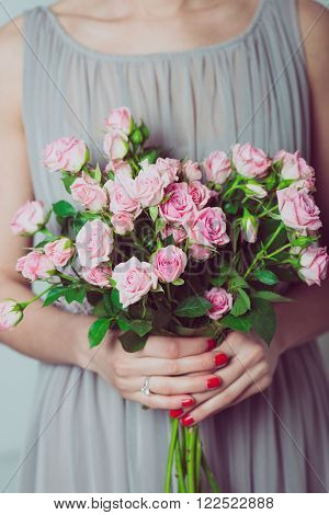 Close up image of bridesmaid with a bouquet of rose flowers