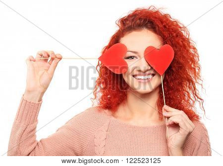 Red-haired young woman holding paper hearts near eyes, isolated on white