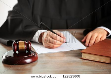Judge writing on paper with gavel on wooden table indoors
