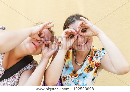 Pretty young women posing for photos put his hands to his eyes like binoculars. Two funny girls fooling around and grimaces. Shallow depth of field. Selective focus.