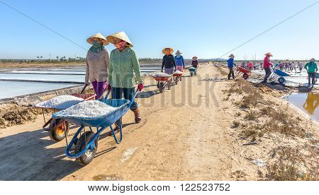 Binh Thuan, Vietnam - January 22nd, 2016: Group fishermen go vertical salt transported to dormitory with smiling face excited harvest is beauty casual labor in morning region sea Binh Thuan, Vietnam