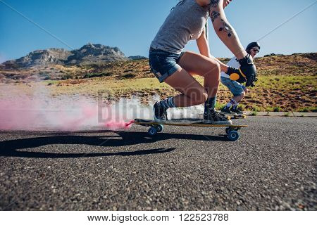Man and woman longboarding down the road. Side view of young people practicing skating outdoors on road.
