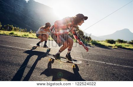 Side portrait of young people skateboarding together on road. Young man and woman longboarding down the road on a sunny day.