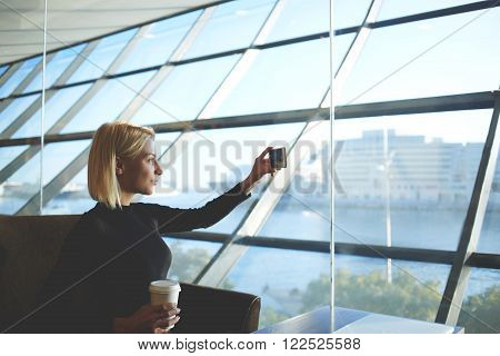 Hipster girl is taking pictures with mobile phone camera for chat with friends while is sitting in airport.Woman is making photo on cell telephone while resting with take away coffee after interview