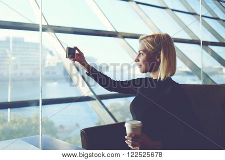 Young woman is taking photo with mobile phone camera, while is sitting with take away coffee is modern office interior