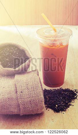 Ice milk tea with tea leaves on wooden background, Vintage style