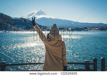 Woman holds Victory at MT.Fuji ( finish travel trip )