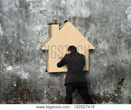 Man pushing wooden house into hole of old mottled concrete wall
