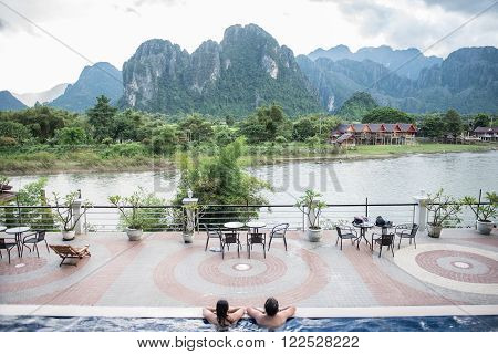 View of the Karst mountains from a hotel in Vang Vieng. Vang Vieng is a riverside party town located on the banks of Nam Song river. Tourists enjoying in a swimming pool are seen.