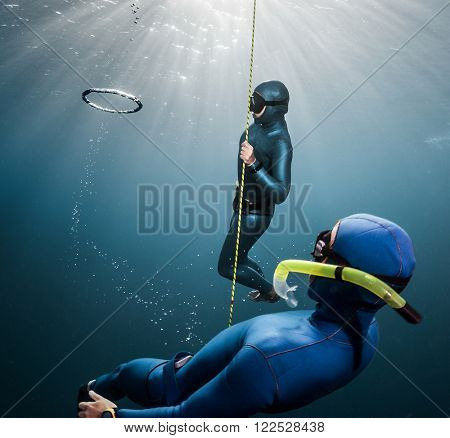 Couple of free divers having fun underwater, making ring bubbles