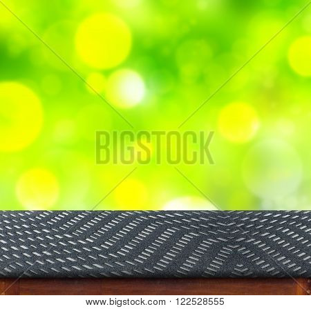 Black zig zag Fabric cover on table with green bokeh background,empty interior for add your product