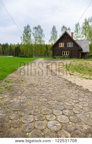 Wooden round log path leading to cottage house blurred background