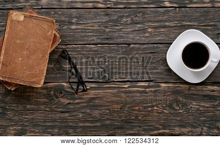 stacked old books eyewear and cup of coffee on a dark wooden table top view with copy space