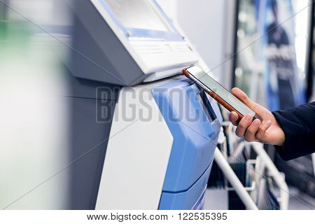 Woman pay with mobile phone by NFC on ticketing terminal