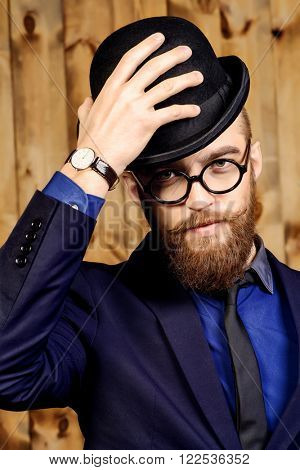 Elegant man wearing suit, bowler hat and spectacles. Old style fashion.