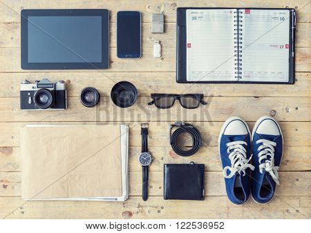 Outfit of a stylish traveler or a freelance journalist. Set of different objects and equipment: tablet, phone, album, glasses, camera, lenses, wallet, gumshoes, usb storage and watches.