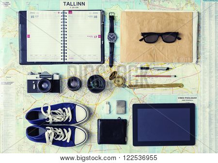 Outfit of a stylish traveler. Set of different objects and equipment: tablet, phone, album, glasses, camera, lenses, gumshoes, magnetic compass and map.