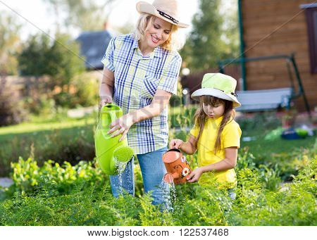 Woman with child little girl watering plants in garden