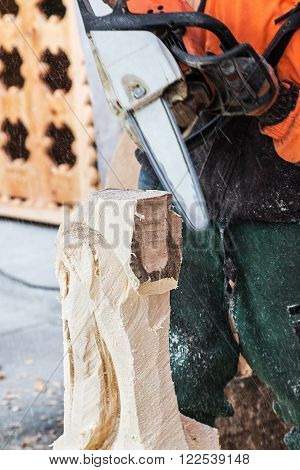 Chainsaw work for figural decoration log. Focus on a log